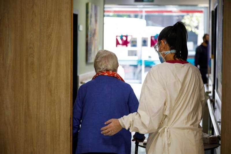 Una trabajadora de una residencia ayuda a caminar a una paciente. EFE