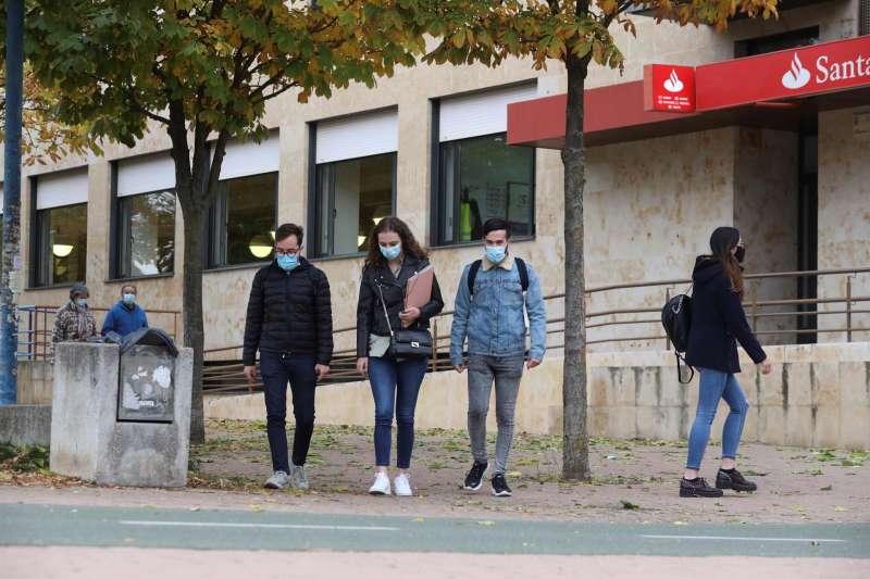 Estudiantes protegidos con mascarillas caminan por la calle. EFE