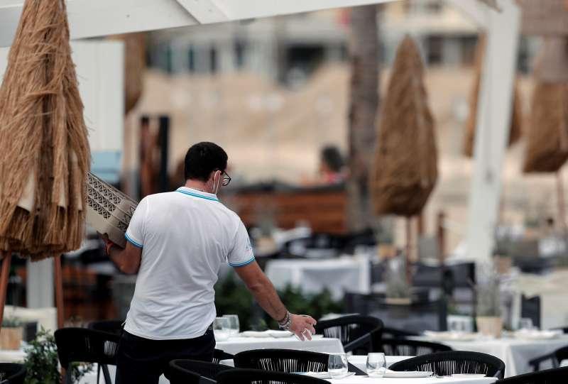 Un camarero recoge una mesa en un bar.