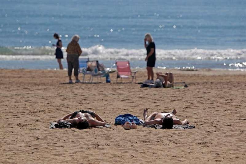 Varias personas disfrutan del buen tiempo y de las altas temperaturas en la playa de El Postiguet. EFE