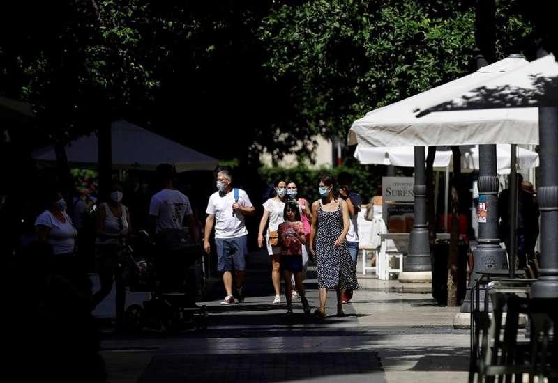 Varias personas, todas ellas con mascarilla, pasean por una zona peatonal.EFE