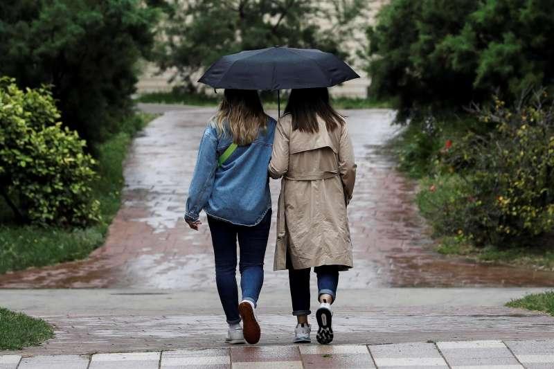 Dos personas se protegen de la lluvia con un paraguas en Valencia. Archivo/EFE/Ana Escobar.
