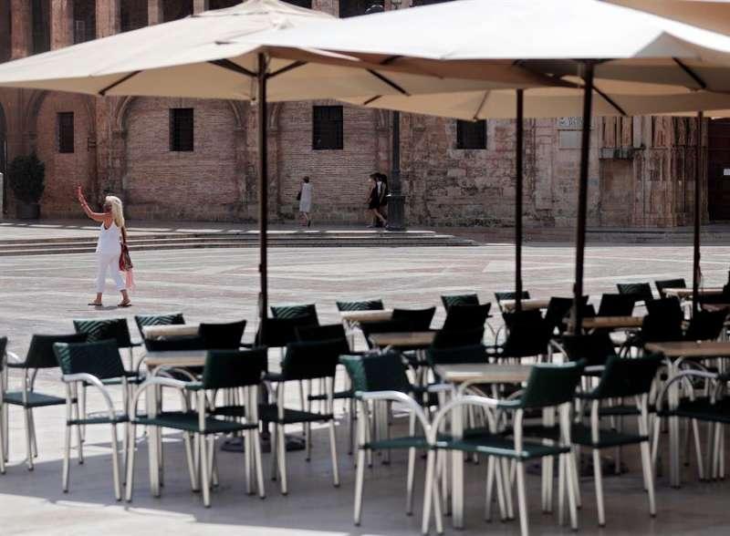 Una persona recorre la plaza de la virgen de València junto a sus terrazas prácticamente desiertas. EFE