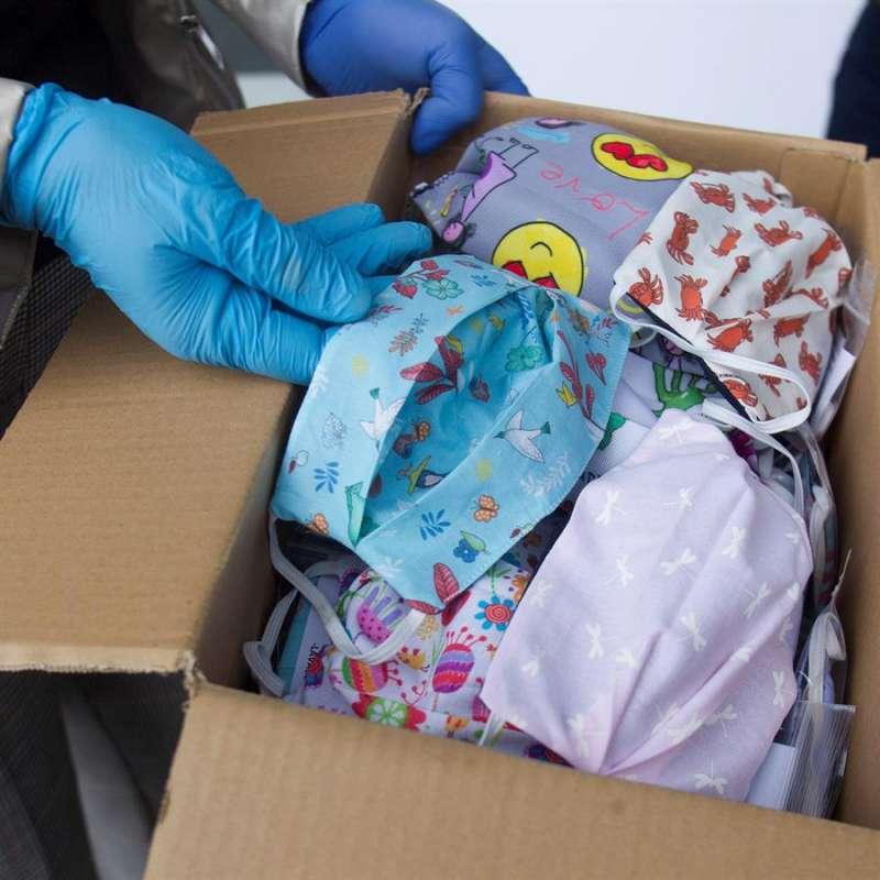 Una persona muestra una caja con mascaraillas. EFE/Archivo