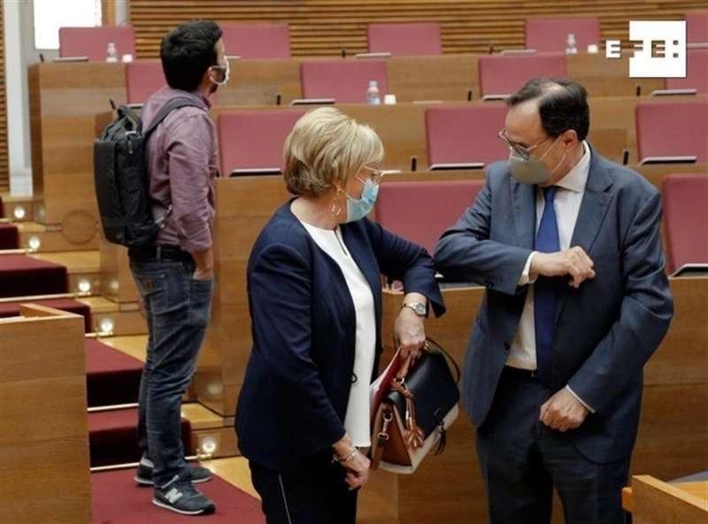 La consellera de Sanidad, Ana Barceló, saluda con el codo al conseller de Hacienda, Vicent Soler, al inicio de la sesión de control, hoy jueves, en Les Corts Valencianes.EFE/ Kai Försterling