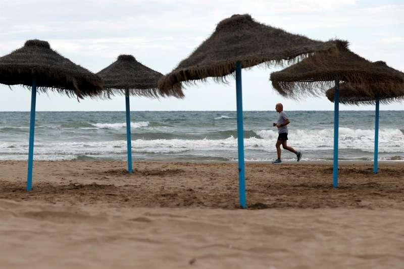 Un hombre corre por la playa de la Malvarrosa en una jornada de tiempo inestable.