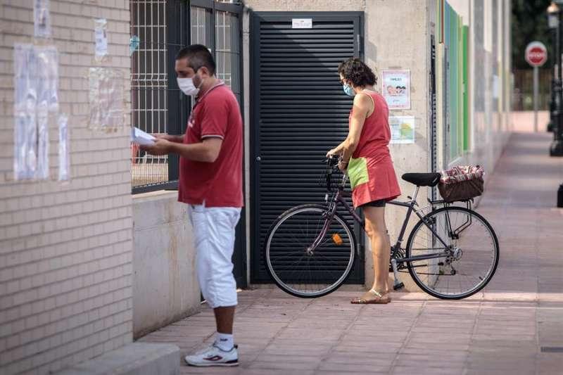 Varias personas esperan a las puertas del colegio de Primaria del CEIP Els Germanells de Rafelbunyol (Valencia), en una imagen de estos. EFE