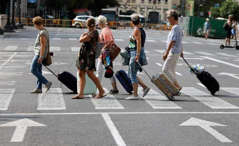 Varias turistas arrastran sus maletas tras abandonar el hotel en Valencia. EFE/ Juan Carlos Cárdenas/Archivo