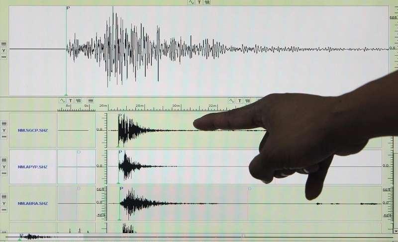 Una persona señala unas gráficas en un sismógrafo.