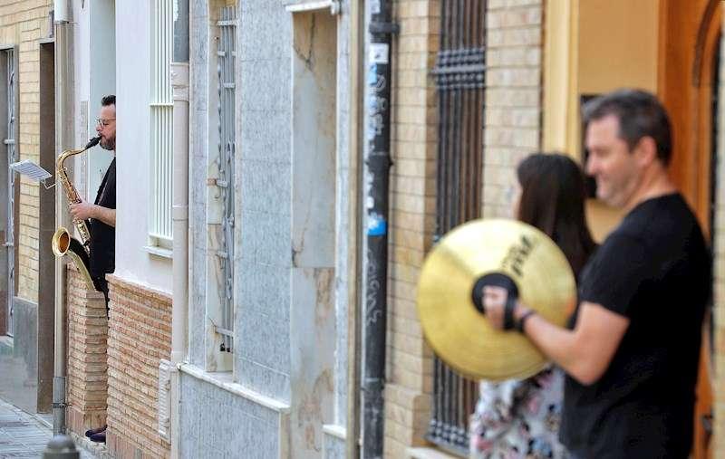 Varios músicos tocan a las puertas de sus casa en el barrio de Benimaclet de Valéncia. EFE