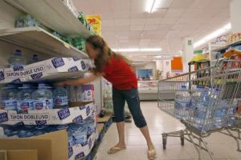 Una mujer coge garrafas de agua de los estantes de un supermercado. EFE