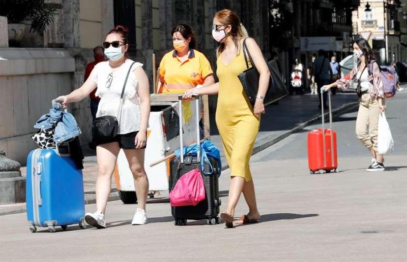Varias mujeres con sus maletas se dirigen a la estación del Norte de Valencia en agosto de 2020. EFE
