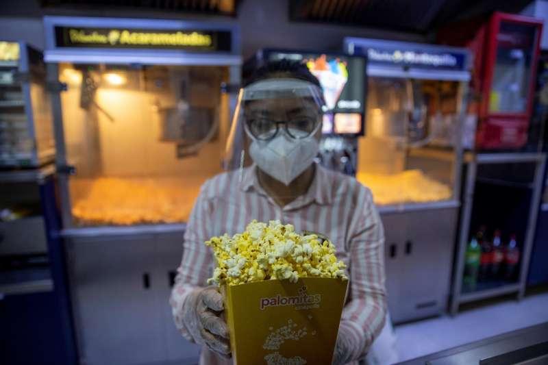 Una mujer ofrece palomitas en una sala de cine.