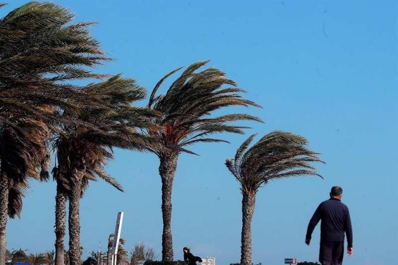 En la imagen, un hombre pasea bajo un fuerte viento. EFE