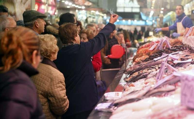 Una señora muestra su turno en una pescaderia del mercado central de València. EFE