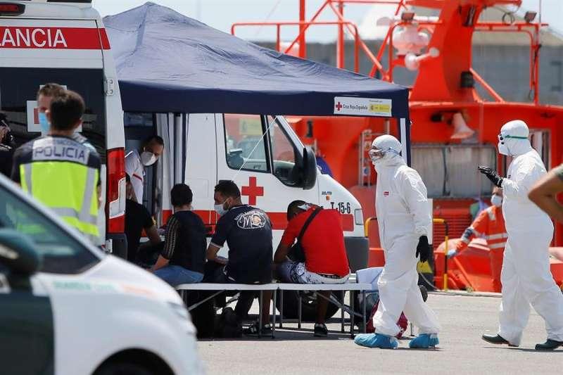Sanitarios de la Cruz Roja, enfundados en EPI, atienden a inmigrantes interceptados tras llegar en patera a Alicante. EFE / Manuel Lorenzo.