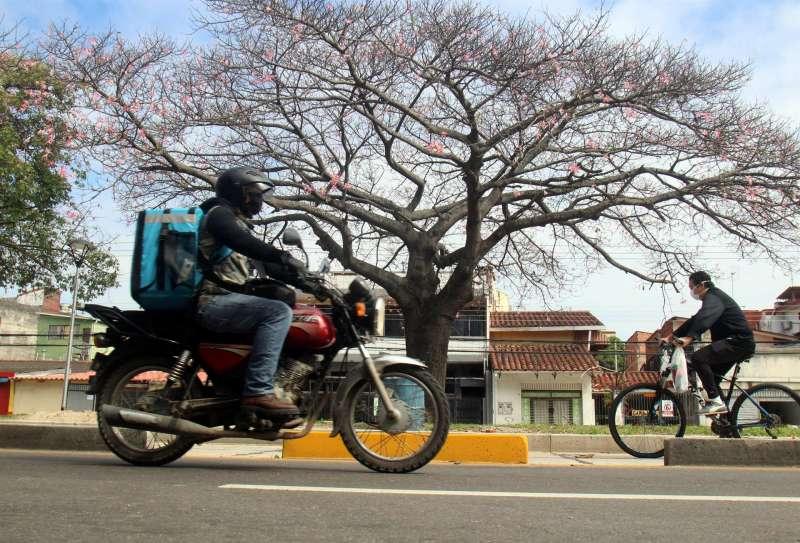 Un repartidor a domicilio trabajando con su motocicleta. EFE