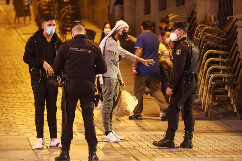 Agentes de Policía Nacional y Local charlan con jóvenes que beben en la calle. EFE