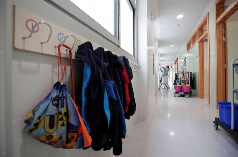 Una trabajadora del servicio de limpieza desinfecta los pasillos de un colegio. EFE/Manuel Bruque/Archivo
