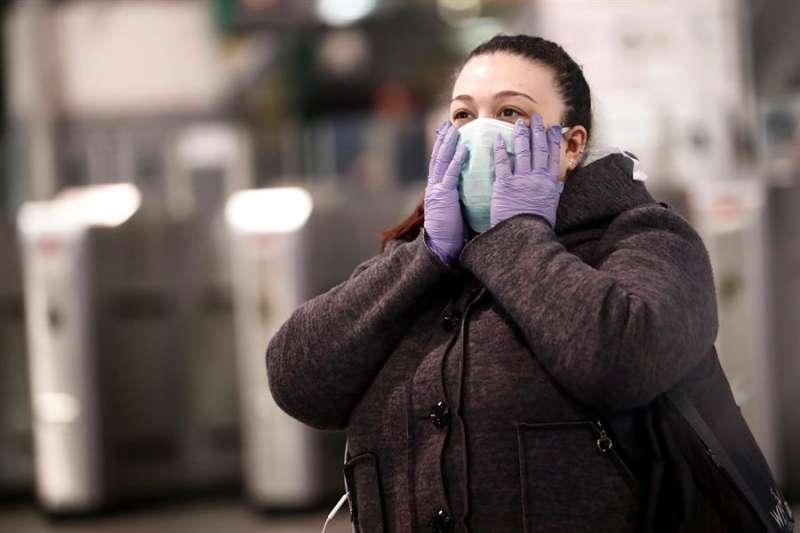Una mujer se protege con una mascarilla. EFE