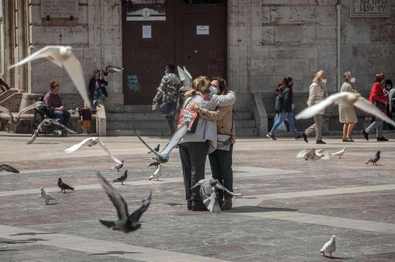 Dos personas se abrazan en una céntrica plaza de València.