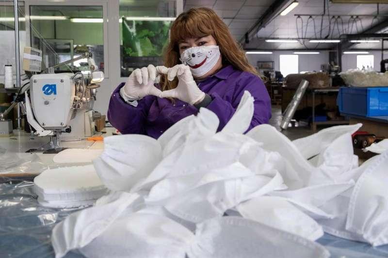 Una trabajadora de un empresa de tapizados trabaja de forma voluntaria en la confección de más de mil mascarillas diarias, que donan de forma gratuita a los hospitales, geriátricos y policía. EFE/Marcial Guillén