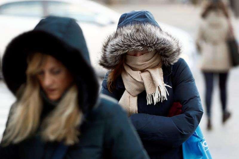 En la imagen, una mujer se protege del frío a primera hora la mañana. EFE