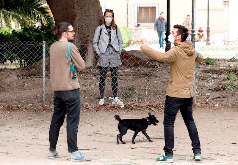 Varias personas pasean a su perro en un parque, en una imagen de estos días de estado de alarma por la pandemia de coronavirus. EFE