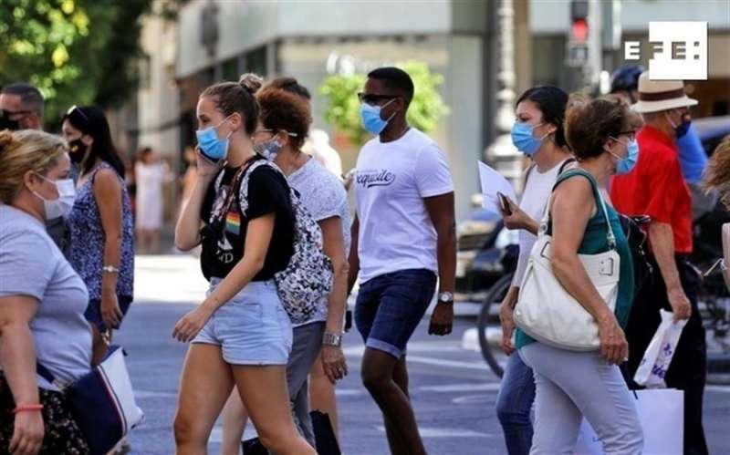 Gente paseando por la calle con mascarilla. EFE