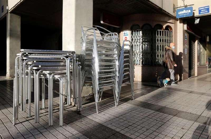 Vista de las mesas y sillas de una terraza apiladas a las puertas de un bar. EFE/Archivo