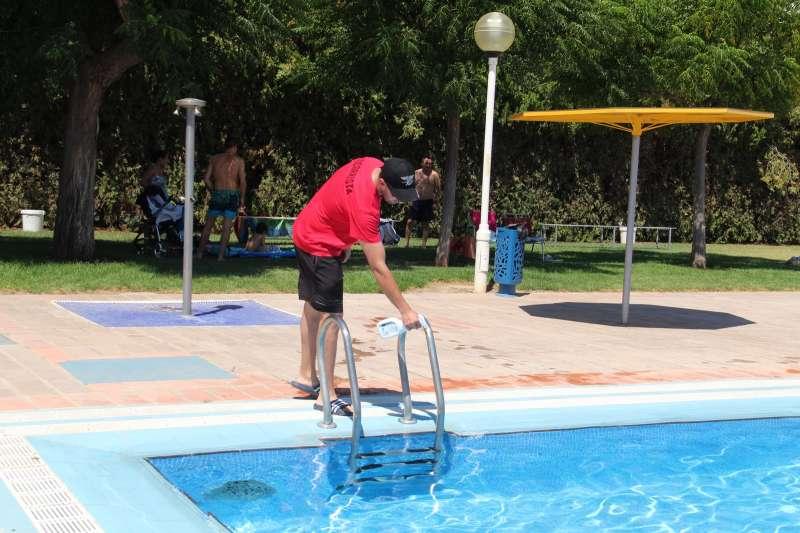 Un operario desinfectando la escalera de la piscina. / EPDA