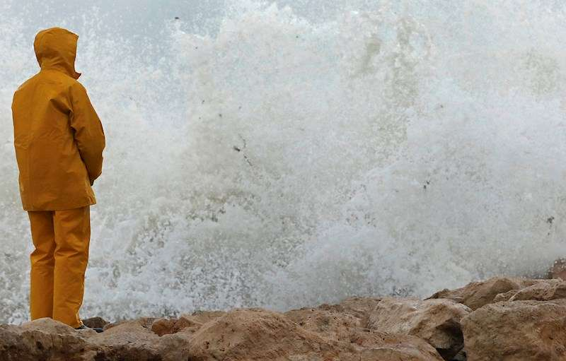 Un hombre observa las olas romper este lunes en el puerto deportivo de Denia tras el paso de la borrasca Gloria. EFE