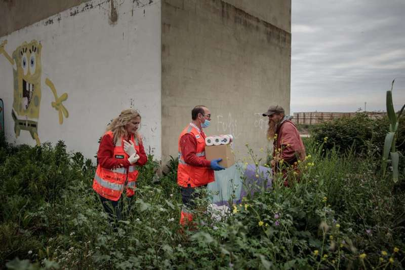Dos voluntarios de la Cruz Roja realizan el reparto semanal de comida y kits de higiene personal a una persona sin hogar. EFE/Biel Aliño/Archivo