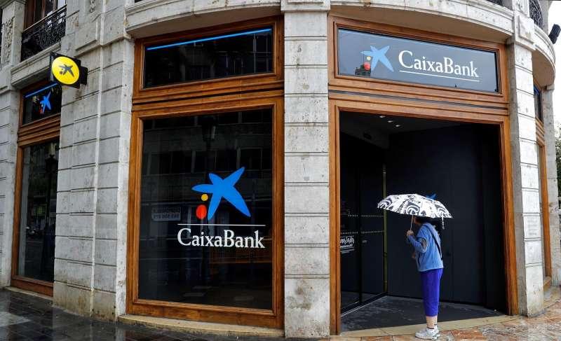 Fotografía de archivo de una mujer que observa el interior de la sede de Caixabank en la plaza del Ayuntamiento de Valencia. EFE