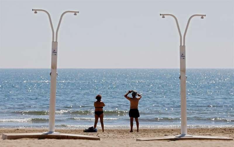 Dos personas disfrutan del buen tiempo y del calor en la playa. EFE/Kai Försterling/Archivo