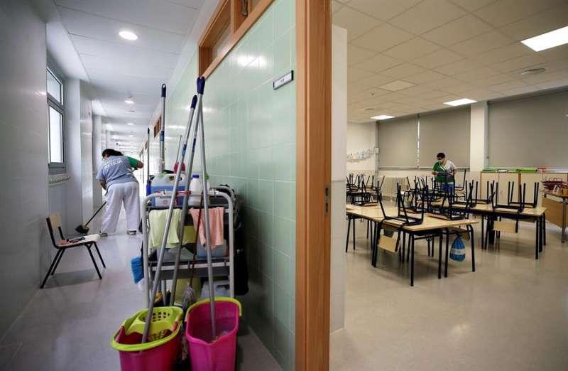 Dos trabajadoras del servicio de limpieza desinfectan los pasillos y las sillas y los pupitres de una clase de infantil. EFE