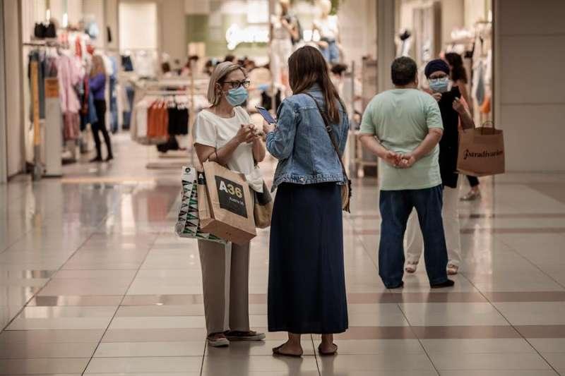 Varias personas realizan compras en un centro comercial con mascarillas. EFE/Biel Aliño/Archivo.