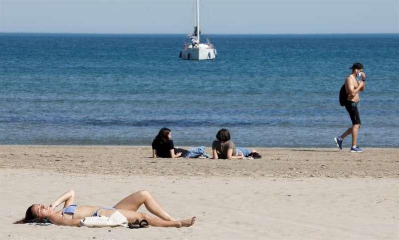 Varias personas toman el sol en la Playa de la Malvarrosa de Valencia en un caluroso día. EFE