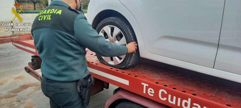 Un agente de la Guardia Civil inspecciona la rueda pinchada de uno de los vehículos afectados. / EPDA