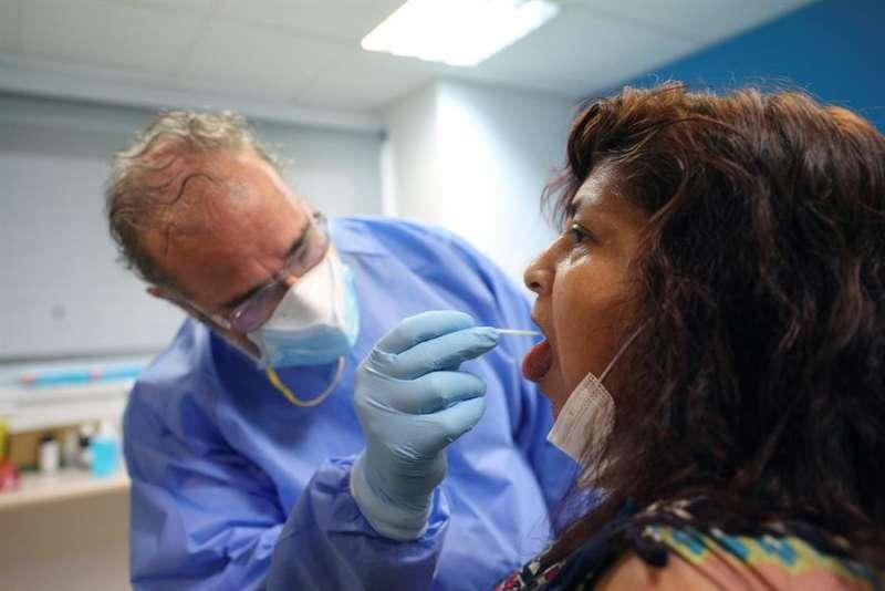 Un sanitario recoge muestras a una paciente. EFE