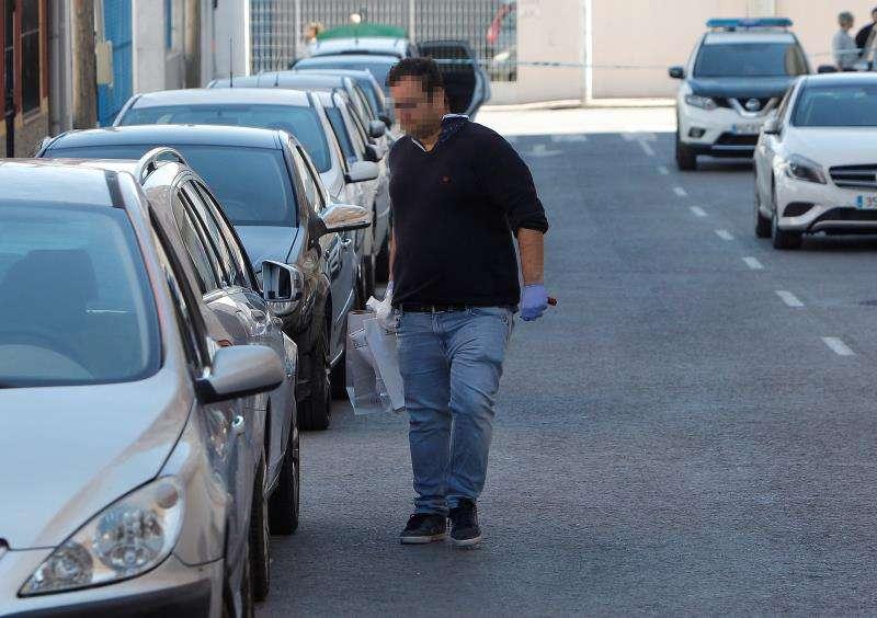 En la imagen, un agente de la policía porta varias bolsas con material recogido en el lugar del hallazgo. EFE