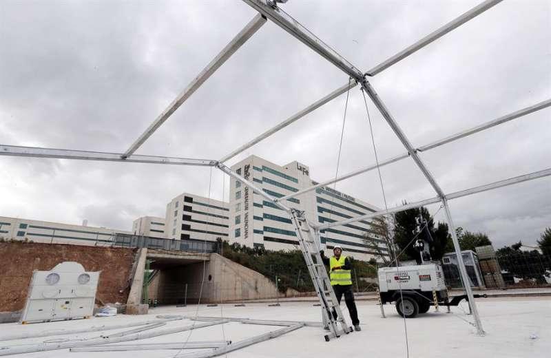 Un operario trabaja en la estructura del hospital de campaña que se está levantando junto al hospital La Fe. EFE/Juan Carlos Cárdenas