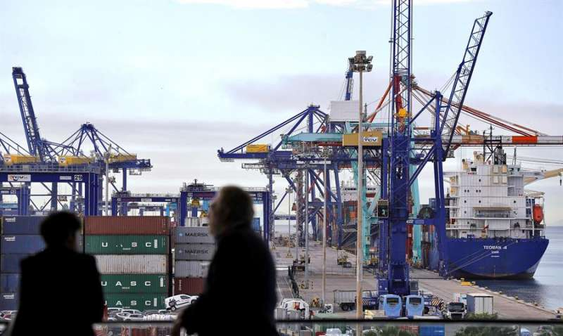 Dos personas observan los trabajos de estiba en varios barcos. EFE/Manuel Bruque/Archivo