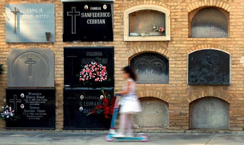 Una niña pasa en patinete ante unos nichos en un cementerio de Valencia. EFE