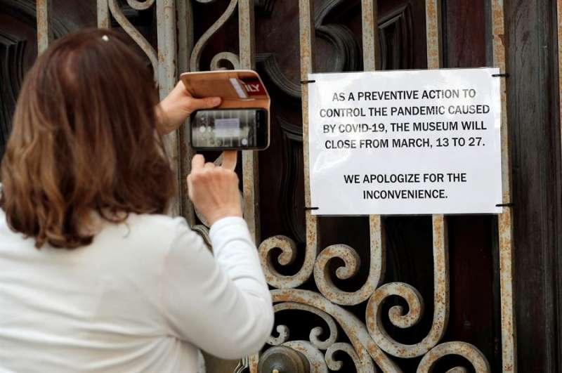Una mujer fotografía el cartel del cierre del Museo Nacional de Cerámica de València por la pandemia de coronavirus. EFE Archivo.
