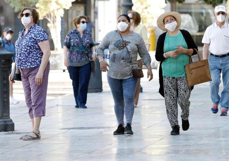 Varias personas caminan por la calle con mascarilla. EFE