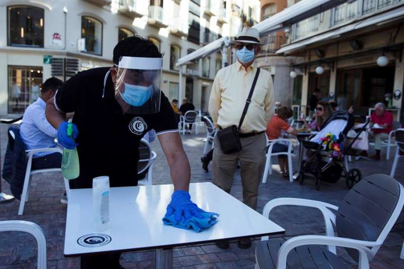 Un camarero desinfecta una mesa en un bar. EFE/Jorge Zapata/Archivo