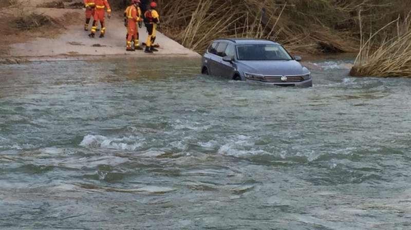 Los bomberos, junto al vehículo hundido en el río Serpis. EFE