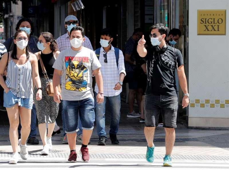 Transeúntes protegidos con mascarillas pasean por una céntrica calle de Valencia. EFE