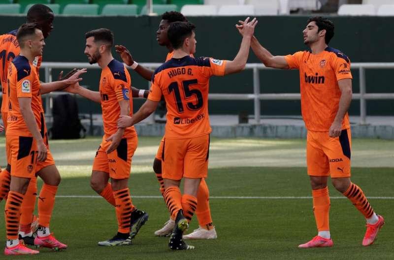 El delantero portugués del Valencia Gonçalo Guedes (d), celebra su gol ante el Betis durante el partido correspondiente a la jornada 33 de LaLiga Santander que estos dos equipos jugaron en el estadio Benito Villamarín. EFE/Julio Muñoz